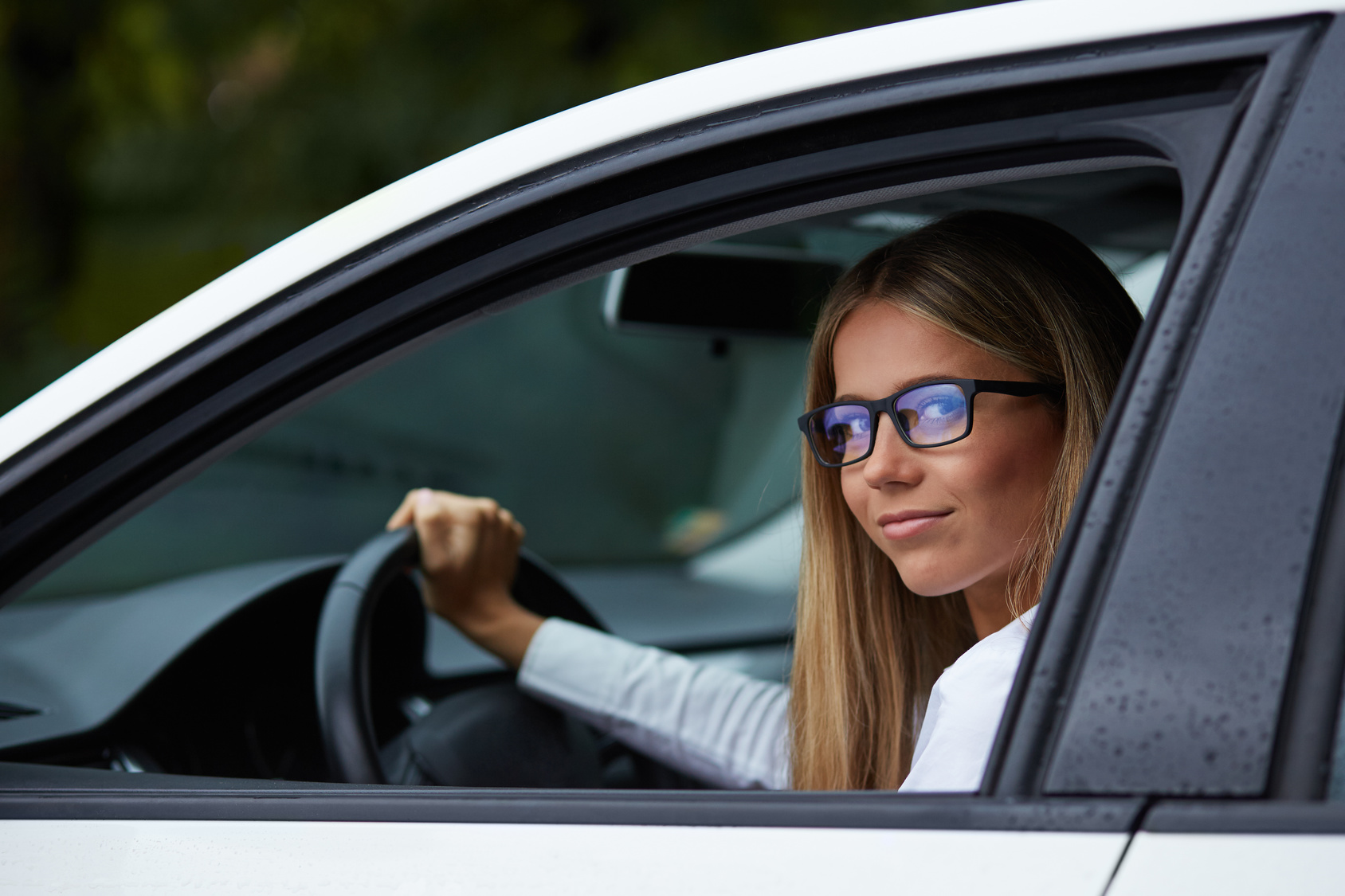 Young woman with glasses driving her car