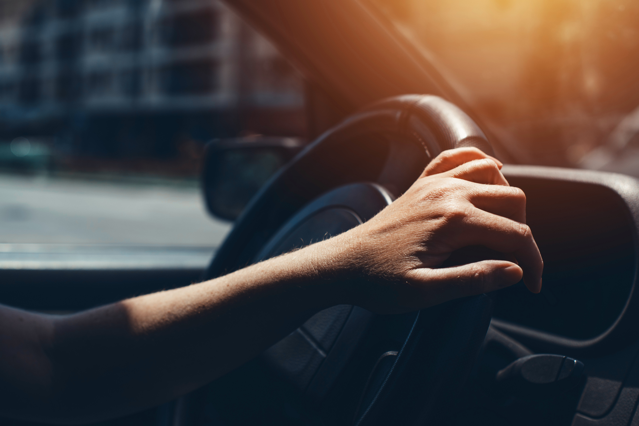 Female hand on car steering wheel, woman driving through city streets on sunny summer day