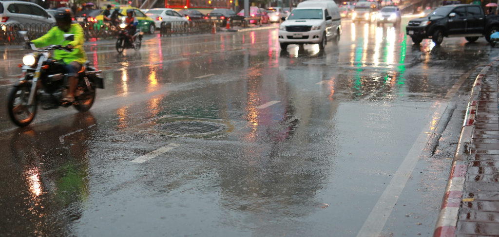Cars in a traffic on a city street on wet road during rain at the morning.
