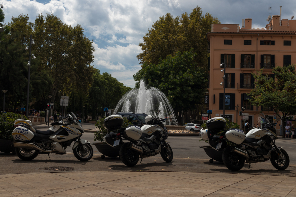Local police motorbikes with fountain in the background; presence due to high number of tourists in Palma de Mallorca historical downtown.